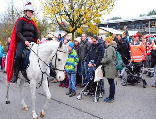 Frau als Sankt Martin reitet auf Pferd