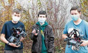 drei Schüler halten ihre Roboter