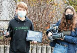 zwei Schüler halten ihre Roboter
