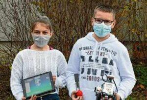 zwei Schüler zeigen ihre Roboter